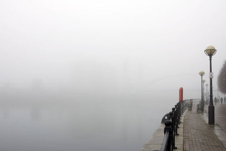 Dense fog above water and people walking on a quayside  Stock Photo