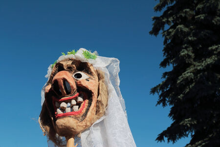 Traditional carved of wood bride mask smiling with big teeth against blue sky and tree.