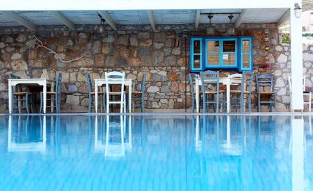 Decorative stone wall with tables and chairs on the poolside reflected in the calm blue outdoor swimming pool water. Stock Photo