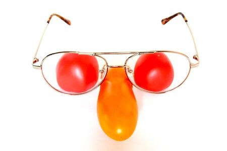 Three tomatoes - one long yellow and two round red ones and old retro aviator style glasses make funny face composition isolated on white background.