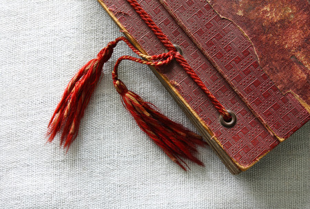 Old worn out red photo album corner with two tassels on flax canvas Stock Photo