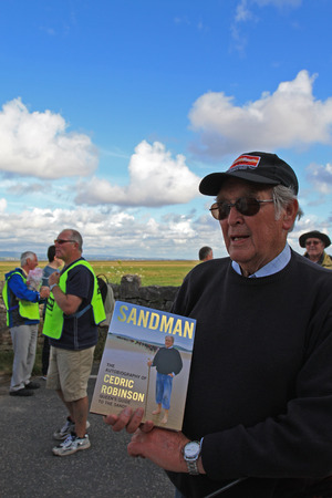 KENTS BANK, UNITED KINGDOM - JULY 29: Mr. Cedric Robinson MBE, official UK Queens Guide to the Sands and author of Sandman and other books is showing his autobiography book at Kents Bank station. Landscape and charity walk organizers in the background Editorial