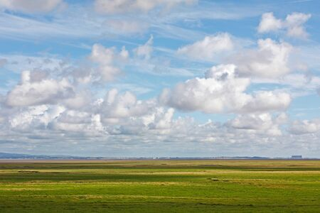 Flat landscape with agricultural land of the Morecambe bay on the north west coast of England,UK with yellow green pasture land on a nice sunny day with blue sky and white clouds. If zoomed at 100% near horizon one can spot a line of people walking across