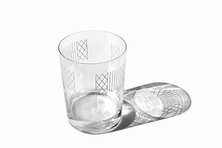 Decorated with ornament clear glass almost empty with shadow isolated on white background. Stock Photo