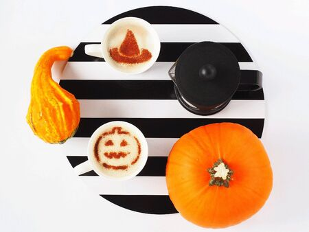 Coffee with topping Halloween, pumpkins and French press on a background of black and white stripes