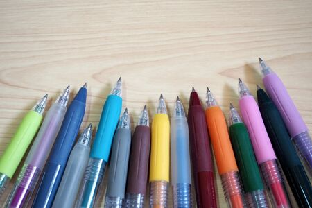 many color Ballpoint Pens on wooden table background