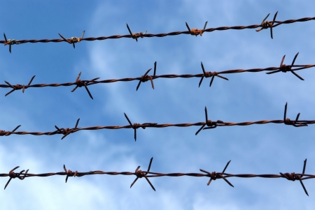 Barb wire fence and blue sky blackground photo