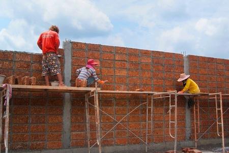 Bangkok  THAILAND - SEP 19   Unidentified Workers are Constructing large laterite brick wall on September 19, 2012 at Phutthamonthon Sai 3 in Bangkon, Thailand Stock Photo - 17091684