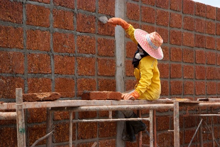 Worker is Constructing large wall with laterite brick