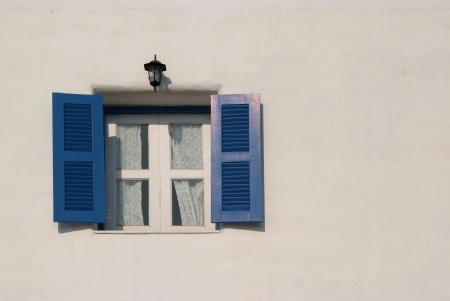 Light and shadow across on the blue window and the white wall.
