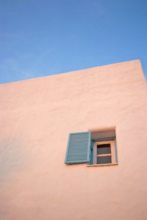 Vintage blue windows on the white wall and blue sky  photo