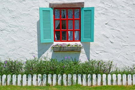 Red and Blue Window with flower pots on the white wall background. photo