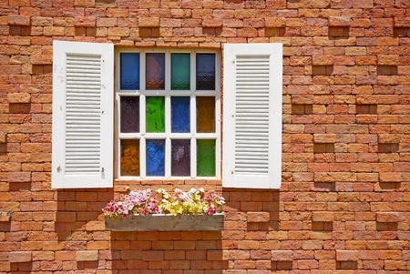 White window with flower pots on the brick wall background. photo