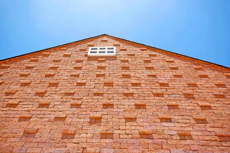 White window on the brick building and blue sky photo