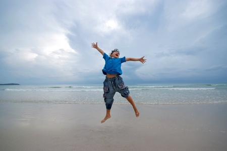 Happy boy jumping on the beach on the morning at Koh Samui, Thailand. photo