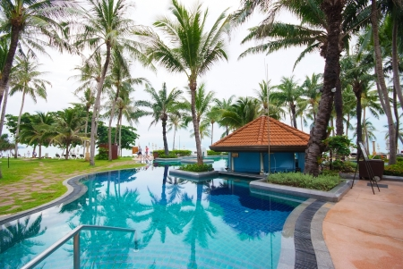Swimming pool beside the sea with coconut tree modern luxury hotel, Samui island, Thailand
