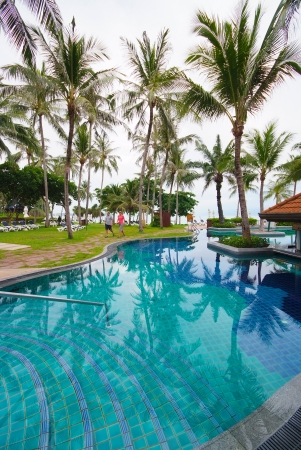 Swimming pool beside the sea with coconut tree modern luxury hotel, Samui island, Thailand