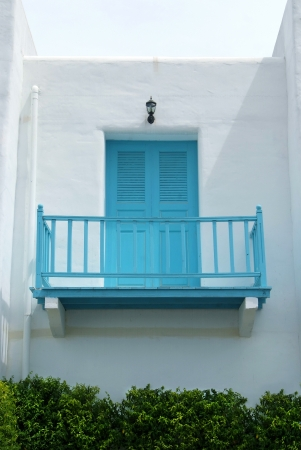Vintage blue door and terrace on the white wall.   photo