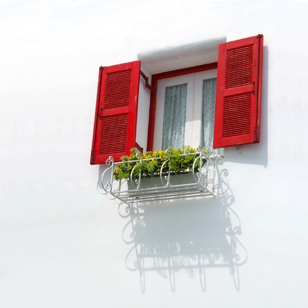 Vintage red window on the white wall and Basket of flowers. photo