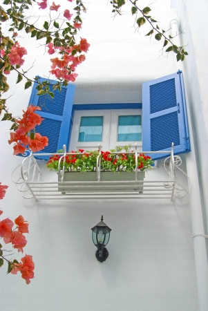 Vintage blue window Decorative with basket flowers on the white wall.  photo