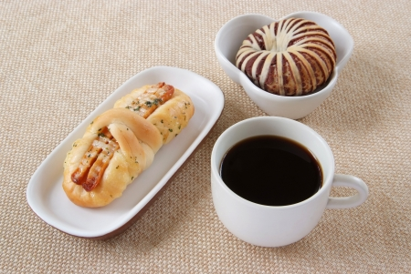 Appetizing sausage, taro bread and cup of coffee on a fabric background  Stock Photo - 22845823