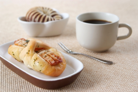 Appetizing sausage, taro bread and cup of coffee on a fabric background  photo