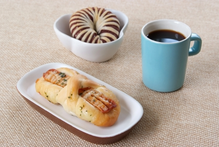Appetizing taro bread, sausage bread and blue cup of coffee on a fabric background Stock Photo - 22854072