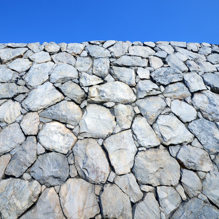Stone wall background and texture with blue sky  photo
