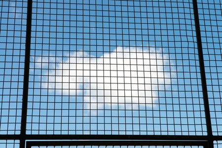 Metal mesh wire fence with blue sky and cloud background