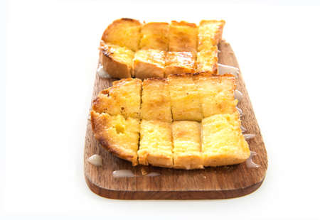 sweetened: Bread toast and condensed milk on wooden plate over white background Stock Photo