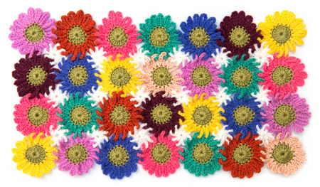 Crochet fabric flowers pattern in white background. Homemade. photo