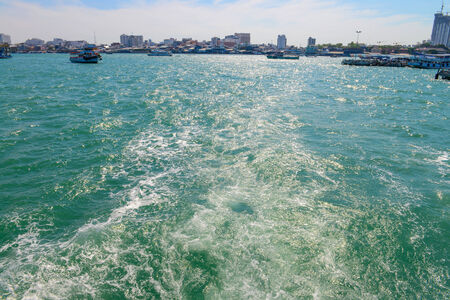 astern: The wake of a boat as seen from the stern of a ship at coast of Pattaya city.