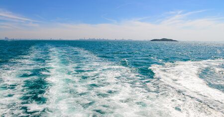 The wake of a boat as seen from the stern of a ship at Coast of Pattaya city, Thailand