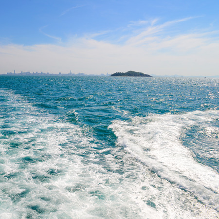 astern: The wake of a boat as seen from the stern of a ship at Coast of Pattaya city, Thailand