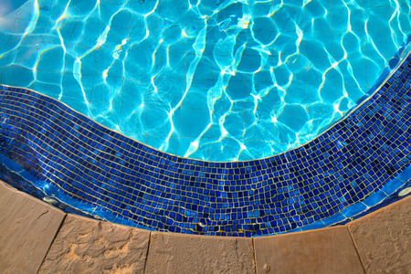 Blue tiles of jacuzzi in the Swimming pool blue water and sunlight reflection effect photo