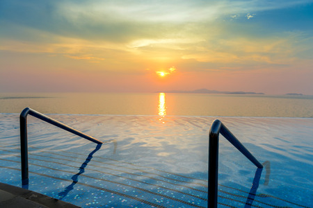 waterpool: Swimming pool with stair and beautiful sunset on the sea at twilight times - Vintage Filter