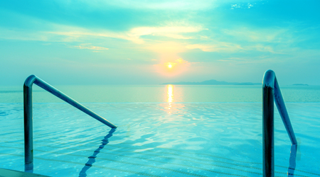 waterpool: Panoramic dramatic view of Infinity Swimming pool with stair and beautiful sunset on the sea at twilight times - Vintage Filter