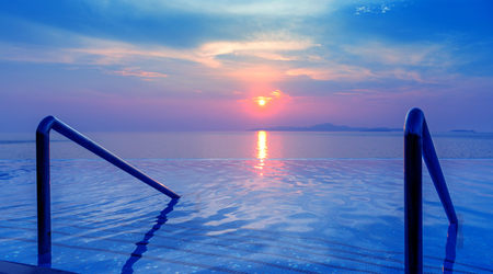 Panoramic dramatic view of Infinity Swimming pool with stair and beautiful sunset on the sea at twilight times - Vintage Filter