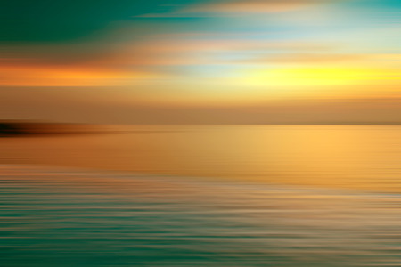 blurred motion: Motion blurred background of refraction in water. Panoramic dramatic view of Infinity sunset on the sea at twilight times.