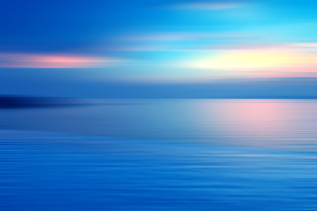vibrant colours: Motion blurred background of refraction in water. Panoramic dramatic view of Infinity sunset on the sea at twilight times.