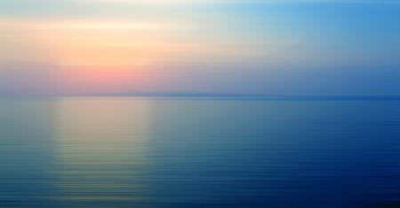 夕暮れ時の夕日と海の上の水の屈折のぼやけている抽象的な背景モーション。
