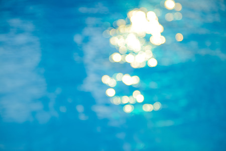 Soft focus bokeh light effects over a rippled, blue water background in the pool.