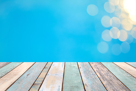 Perspective wood table top and blurry blue water bokeh abstract background, product display montage