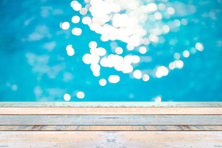 Perspective wood table top and Soft focus bokeh light effects over a rippled, blue water background in the pool, product display montage