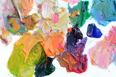 Colorful oil paint of different colors on a palette and brushes on white background Stock Photo