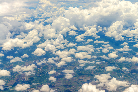 Beautiful view of blue sky above the white clouds and land background from airplane window