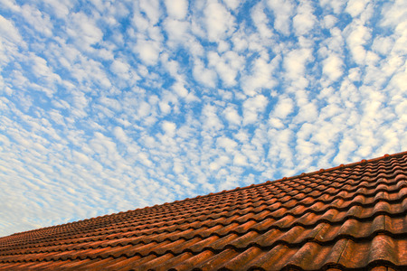 Red house roof and blue sky with white fluffy clouds