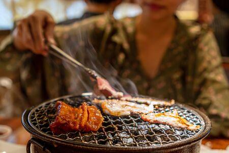 Las mujeres asan carne de cerdo cruda sobre estufa de carbón, barbacoa coreana o al estilo yakiniku.