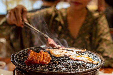 Women grilled raw pork over charcoal stove ,Korean barbecue or yakiniku style.