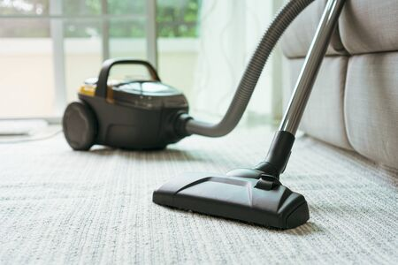 Vacuum cleaner place on the carpet in the living room.